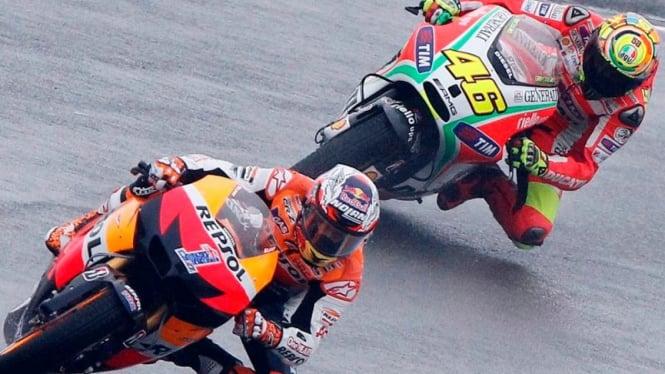 Pembalap Honda, Casey Stoner, bersaing dengan Valentino Rossi