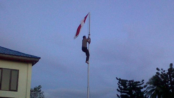 polisi panjat tiang untuk turunkan bendera