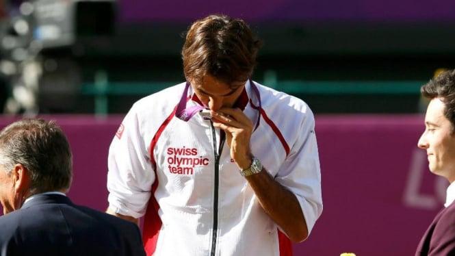 Petenis Swiss, Roger Federer, mencium medali perak di Olimpiade 2012