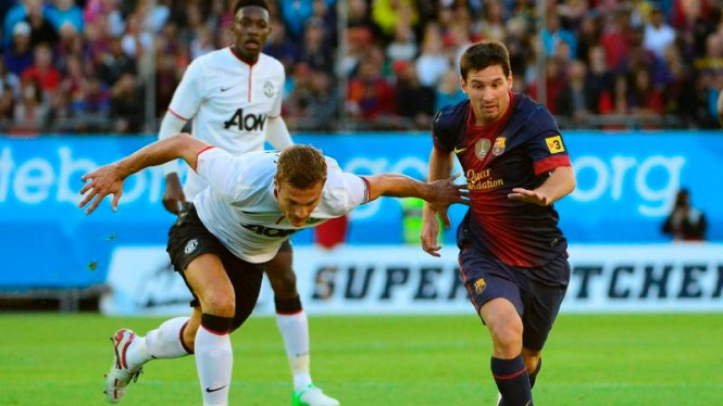Penyerang Barcelona, Lionel Messi, melewati Nemanja Vidic