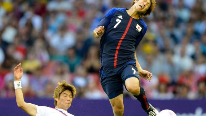 Pemain Jepang, Yuki Otsu (kanan) ditekel pemain Korea Selatan, Ki Sungyueng.