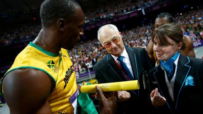 Usain Bolt (kiri) berdebat dengan ofisial pertandingan soal tongkat