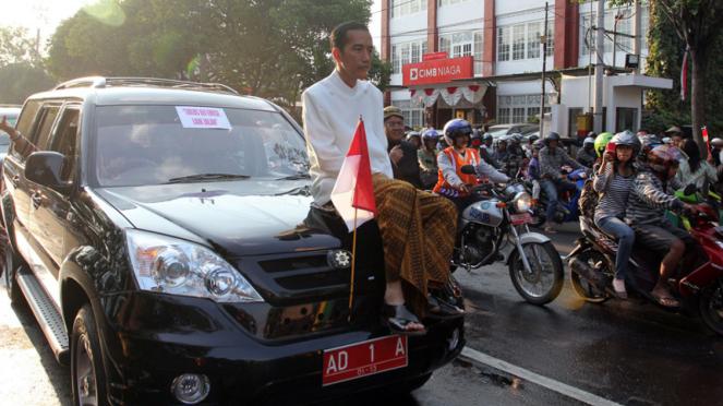 Joko Widodo duduk di atas kap mesin mobil Esemka yang telah dinyatakan lolos uji emisi. Saat itu Jokowi masih menjabat Wali Kota Solo.