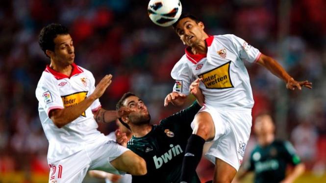 Pemain Sevilla mengepung pemain Real Madrid, Gonzalo Higuain (hitam)