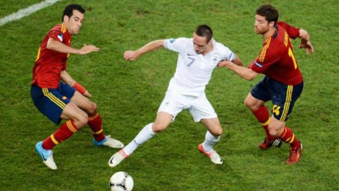 Pemain Prancis, Frank Ribery (putih), diapit pemain Spanyol di Euro 2012