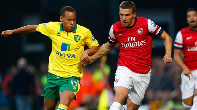 Striker Arsenal, Lukas Podolski (kanan) berebut bola dengan pemain Norwich
