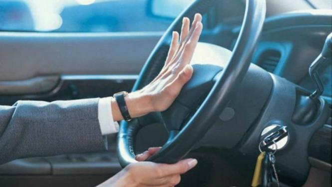 Pengemudi membunyikan klakson saat mengendarai mobil