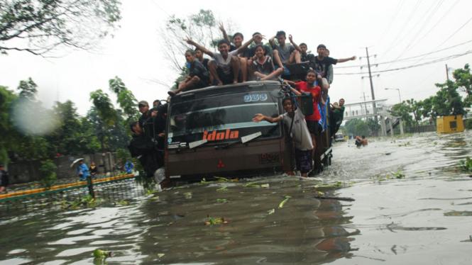 Menaiki Kendaraan Besar Untuk Melintasi Banjir