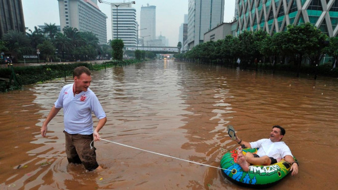 Dua Turis Menikmati Banjir Jakarta