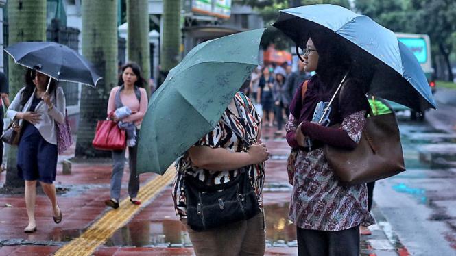 Warga Jakarta berpayung di kala hujan.