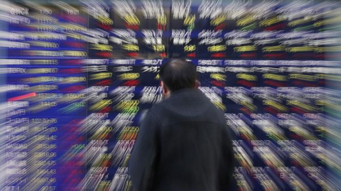 Pria melihat papan indeks saham di tokyo