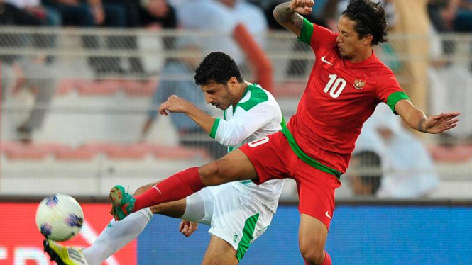 Pemain Timnas Indonesia, Irfan Bachdim (merah), berjibaku melawan Irak