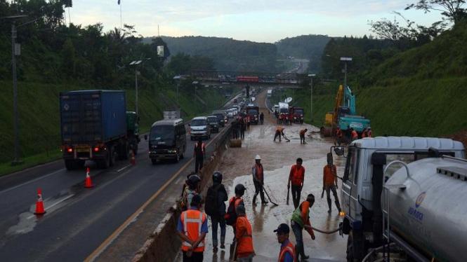 Petugas membersihkan lumpur sisa longsor di jalur tol Cipularang Km 100.