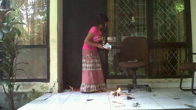 Warga Denpasar membersihkan ulat bulu yang menyerang rumah mereka.