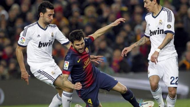 Dua pemain Real Madrid mengapit pemain Barcelona, Cesc Fabregas