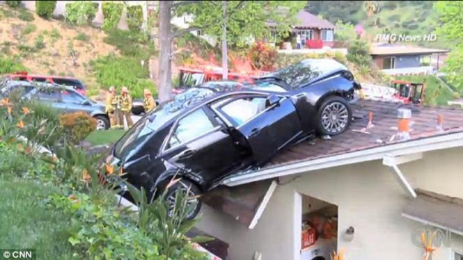 kecelakaan mobil tersangkut di atap rumah