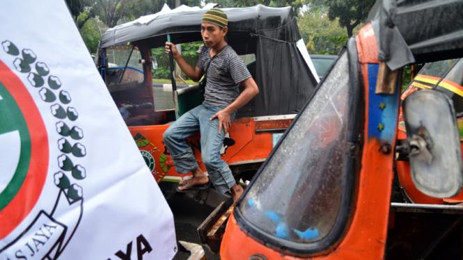 Puluhan sopir bajaj melakukan aksi unjuk rasa di depan kantor Gubernur DKI Jakarta, Kamis (4/7/2013).