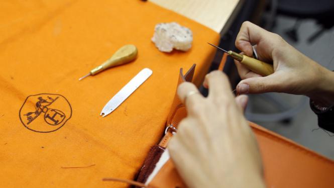 Seorang pengrajin menyelesaikan pembuatan kelly bag di pabrik Hermes di  Seloncourt 4a622f026c