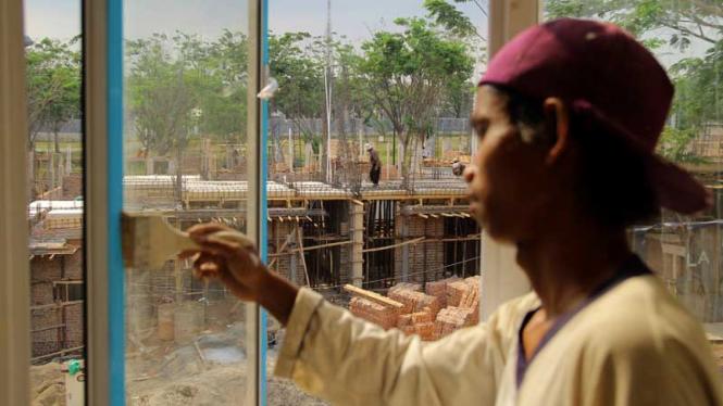 Pekerja melakukan proses pembangunan rumah
