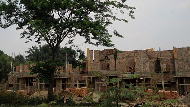Pekerja menyelesaikan proses pembangunan rumah