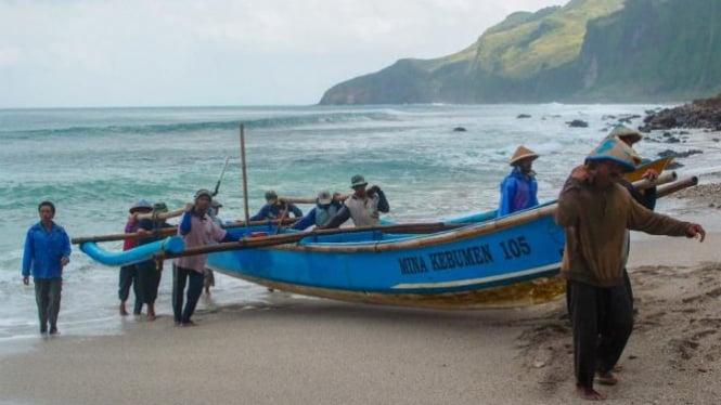 Nelayan Menganti bergotongroyong menepikan perahu.