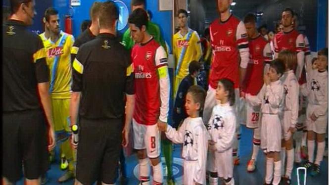 Bocah maskot menangis digandeng Mikel Arteta (nomor 8)