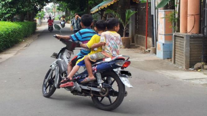 Anak-anak mengendarai sepeda motor.