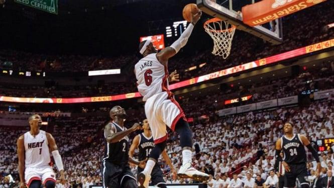 Pemain Miami Heat, LeBron James, memasukan bola