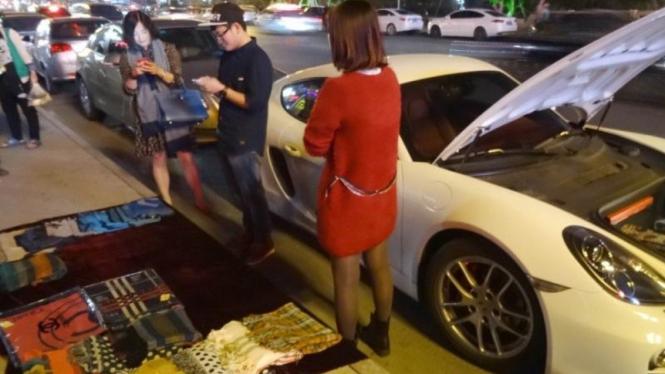 Pria bermobil Porsche yang menjual syal di China.