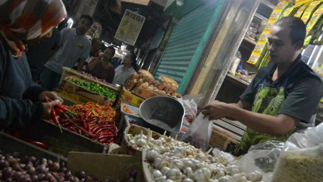 Seorang pembeli sedang memilih cabe keriting di pasar.