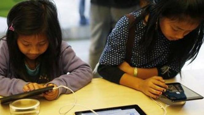 Anak-anak asyik bermain gadget.
