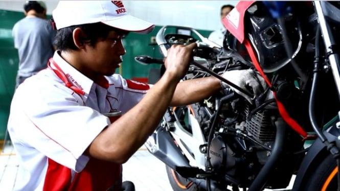 Seorang montir tengah melakukan servis sepeda motor.
