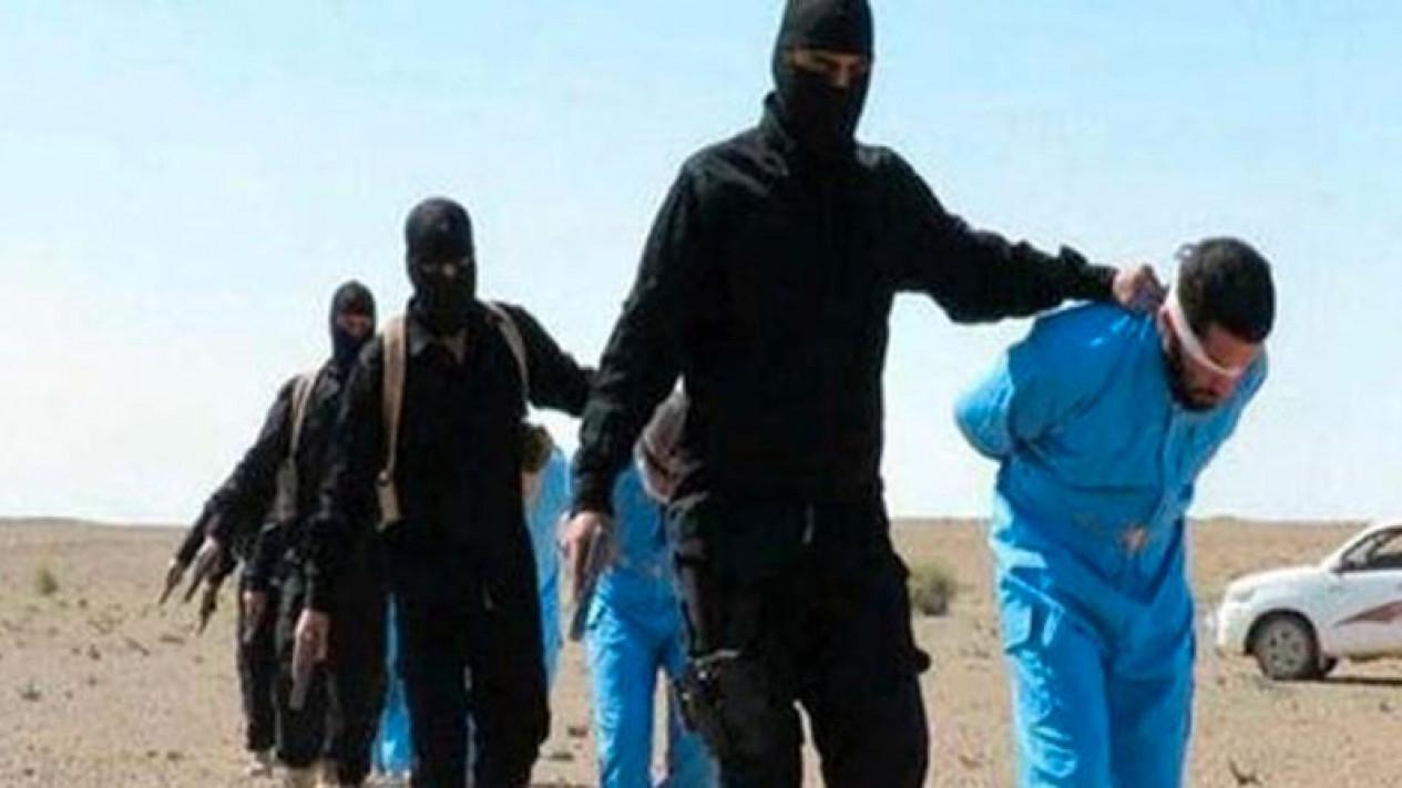 Kelompok militan ISIS dengan tahanan berbaju biru. Foto ilustrasi.