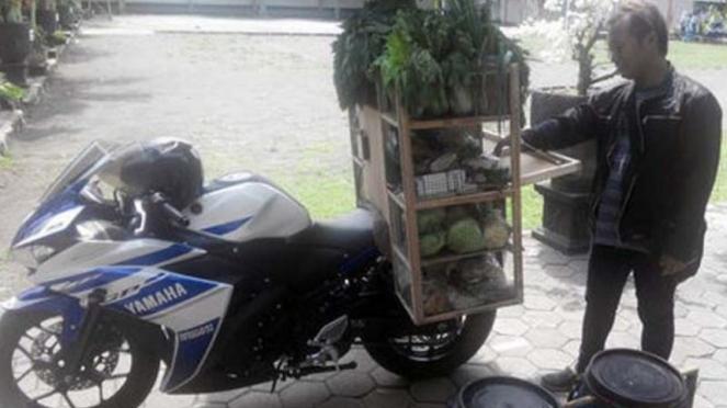 Tanto Dwi Anggoro bersama motor dan dagangannya.