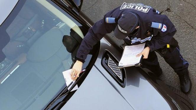 Ilustrasi polisi memberi surat tilang.