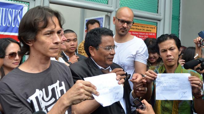 Guru Jakarta International School (JIS) Ferdinand Tjiong (kiri) dan Neil Bantleman (kedua kanan) menujukkan surat keputusan bebas saat keluar dari Rutan Cipinang, Jakarta, Jumat (14/8/2015).