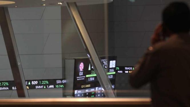 Seorang karyawan BEI mengamati layar indek saham di Bursa Efek Indonesia (BEI)