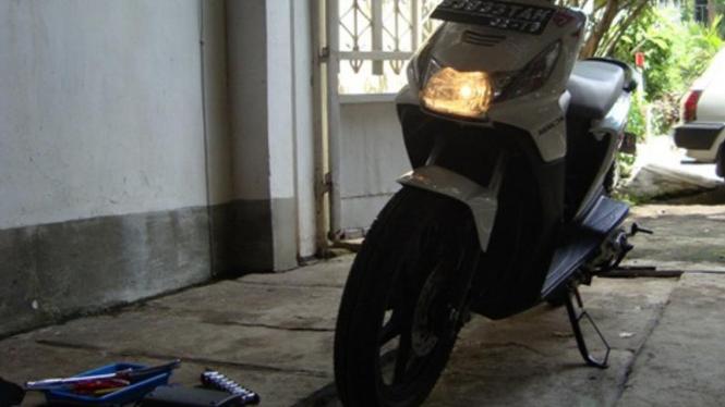 Memarkir motor dengan standar miring.