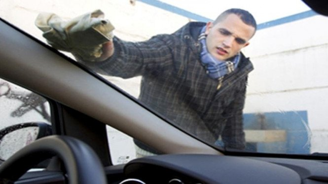 Membersihkan kaca mobil.