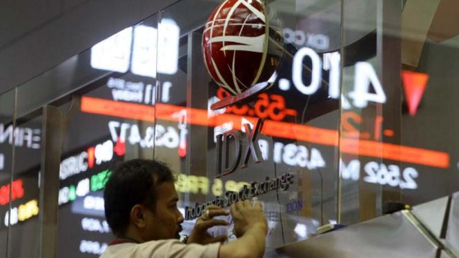 Pekerja membersihkan kaca di Bursa Efek Indonesia, Jakarta.
