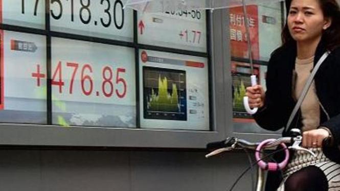 Warga Jepang mengendarai sepeda di depan papan bursa Jepang.