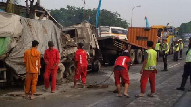 Petugas evakuasi bangkai truk yang terbakar di Tol Cawang.