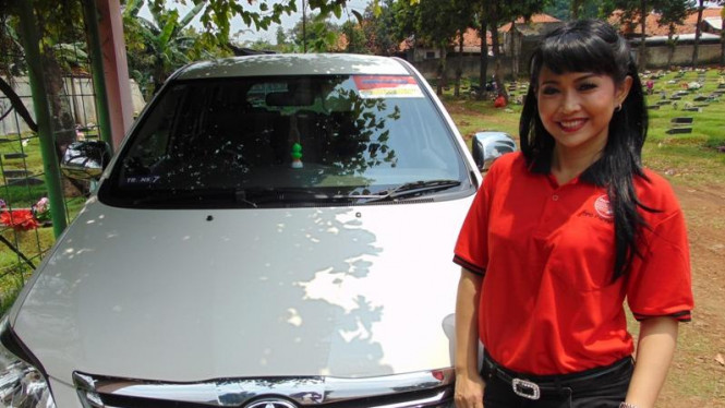Ratna Listy di depan mobil kesayangannya.