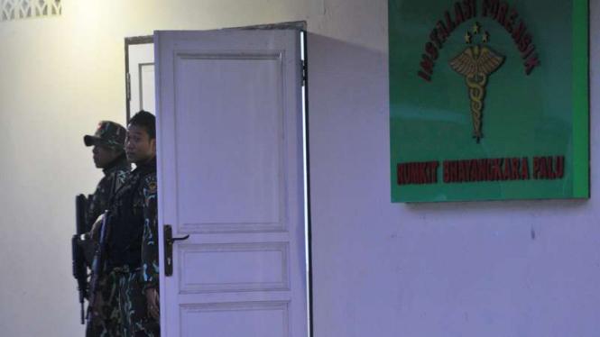 Dua anggota Brimob berjaga di depan pintu masuk ruang instalasi forensik tempat terduga teroris diperiksa di Rumah sakit Bhayangkara, Palu, Sulawesi Tengah, Senin (29/2/2016).