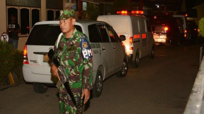 Prajurit TNI bersiaga di sekitar mobil ambulans yang mengangkut Jenazah korban jatuhnya helikopter milik TNI di Poso saat tiba di Rumah Sakit Bhayangkara Palu, Sulawesi Tengah, Senin (21/3/2016)