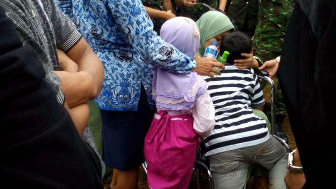 Istri Mayor Cpm Anumerta Agung K. saat memeluk kedua anaknya