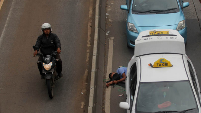 Pengendara motor melintas di dekat sopir taksi yang tertidur saat melakukan demo menolak keberadaan angkutan umum online di di Jalan Gatot Subroto, Senayan, Jakarta, Selasa(22/3/2016).