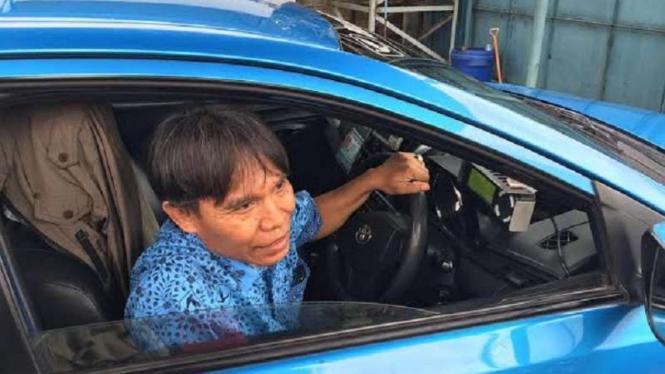 Karmono saat mengemudikan taksinya.