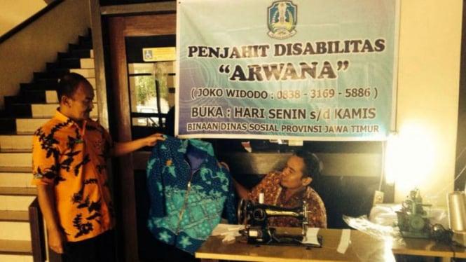 Joko Widodo (kanan-duduk), warga Surabaya penyandang disabilitas, dengan lapak menjahitnya di kantor Dinas Sosial Pemerintah Provinsi Jawa Timur pada Rabu, 23 Maret 2016.