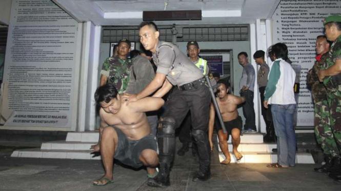 Petugas gabungan TNI dan POLRI mengevakuasi tahanan saat kebakaran yang dipicu aksi tawuran dan tembak menembak antar napi di Lembaga Permasyarakatan (Lapas) Kelas II A Malabero Kota Bengkulu, Jumat (25/3/2016)